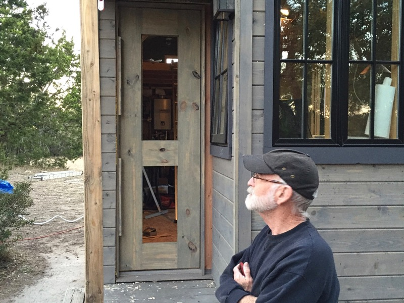 Photo of Alva in front of the Tiny House